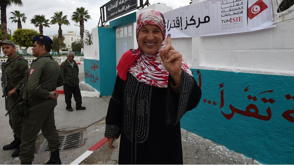 A Tunisian woman voter showcases her ink-stained index finger after voting in the first free municipal elections since the 2011 revolution