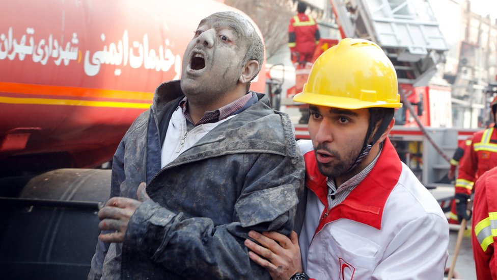 Rescue worker helps an injured man after building collapse in Tehran, Iran (19 January 2017)