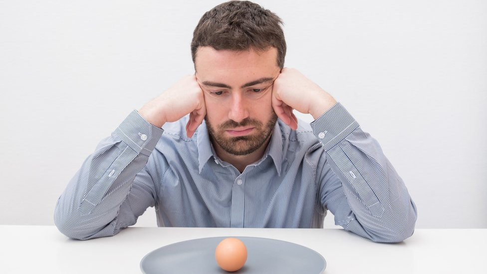 Hombre joven mirando a un plato con un huevo con cáscara.