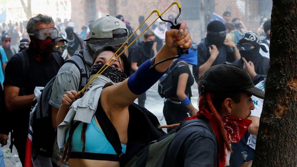 محتجة تضرب قوات الشرطة بالمقلاع