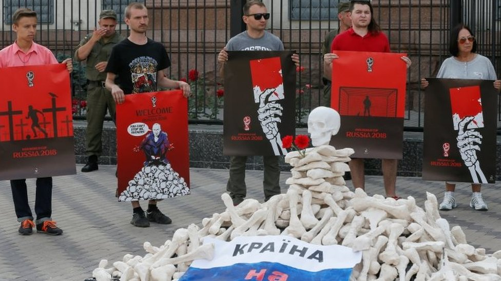Protesters in front of the Russian embassy in Kiev hold posters by artist Andriy Yermolenko, urging for the boycott of the World Cup in Russia. Photo: 14 June 2018