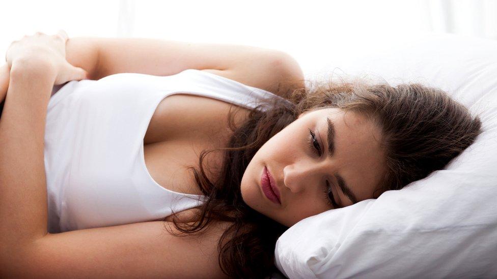 Mujer joven en la cama con cara triste.