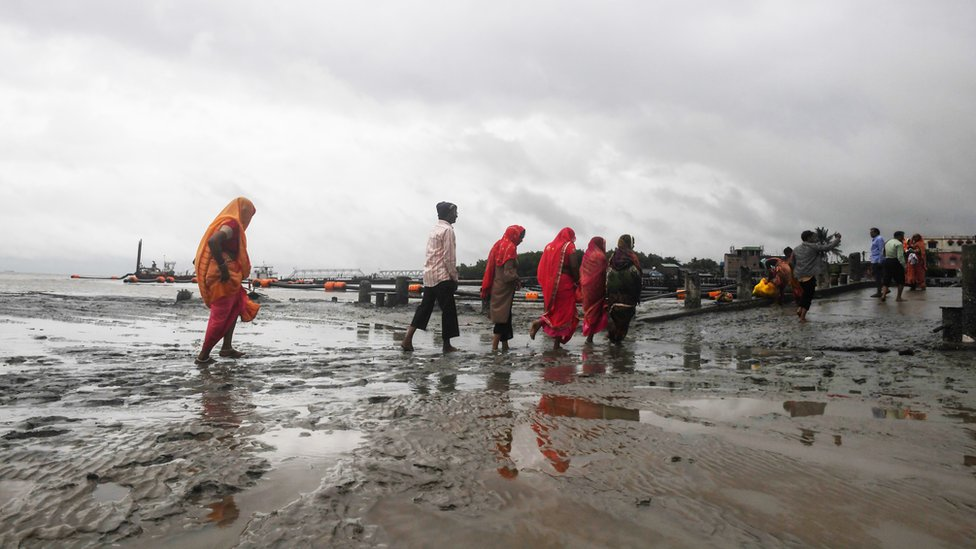 Hindu pilgrims walk back from the dock after a ferry service to Sagar Island was suspended due to Cyclone Bulbul