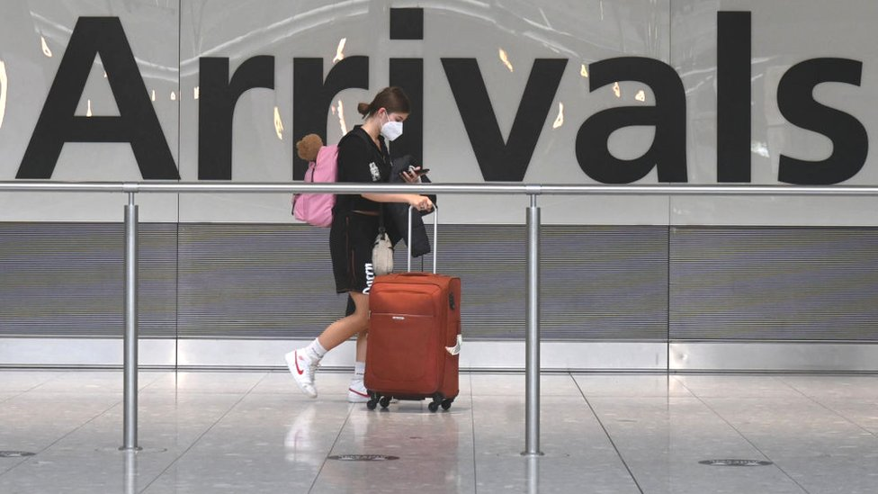Passenger in face mask in airport arrivals hall