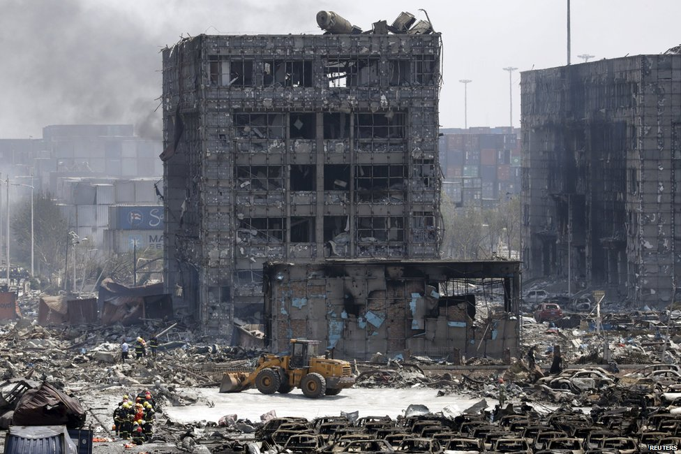 Damaged buildings and cars are seen near the site of the explosions at the Binhai new district, Tianjin, August 13, 2015.