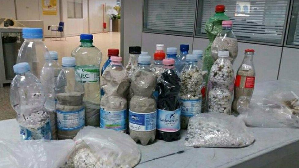 Turistler Sardinya sahillerinden kum ve çakıl taşlarını pet şişelere doldurup hatıra olarak evlerine götürmek istiyor.
