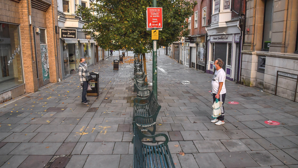 Two friends, both wearing masks, talk to each other from either side of an empty pedestrianised shopping street in Newport, Wales