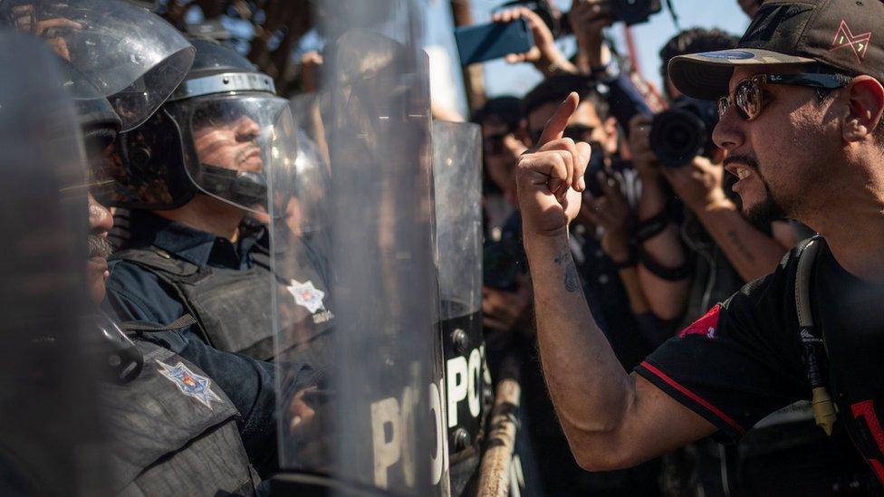 Demonstranti viču na policajce koji obezbeđuju prihvatni centar za izbeglice u Tihuani