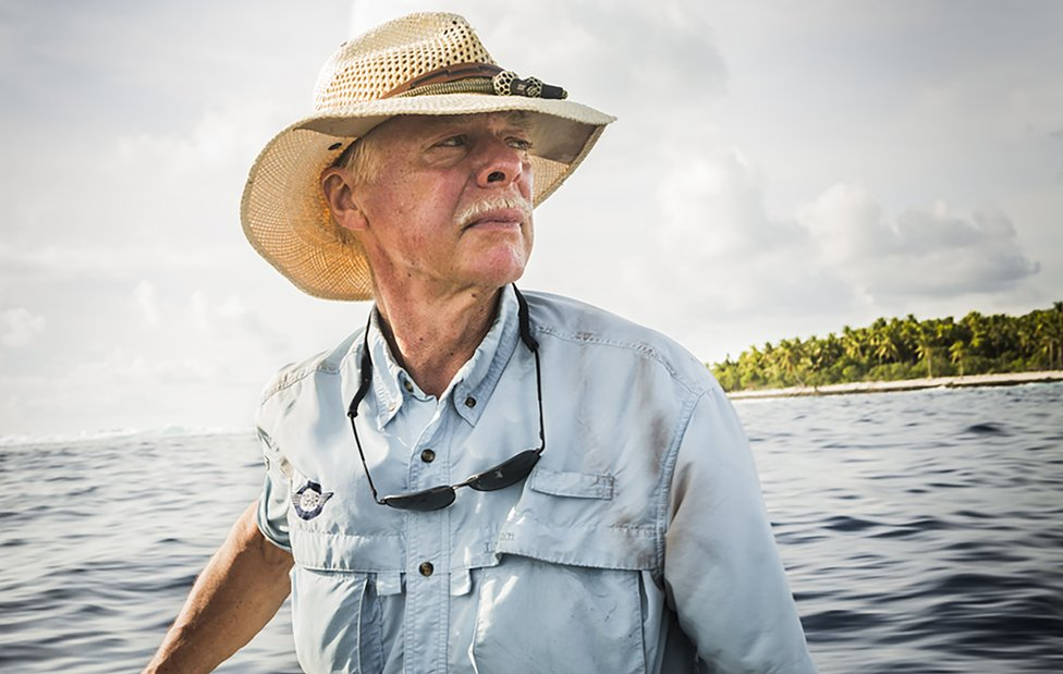 A picture of Ric Gillespie at sea in a straw hat and blue shirt