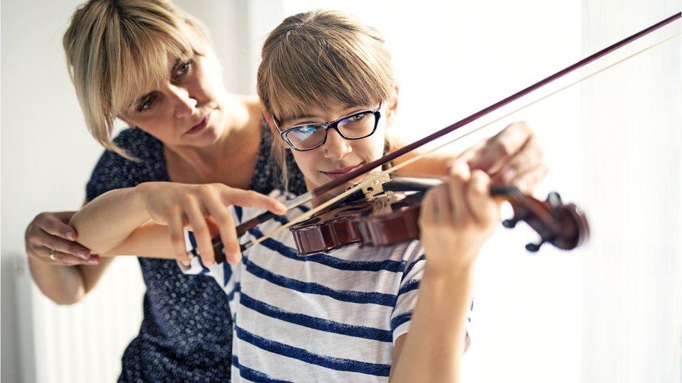 Mujer enseñando a niña a tocar violín.