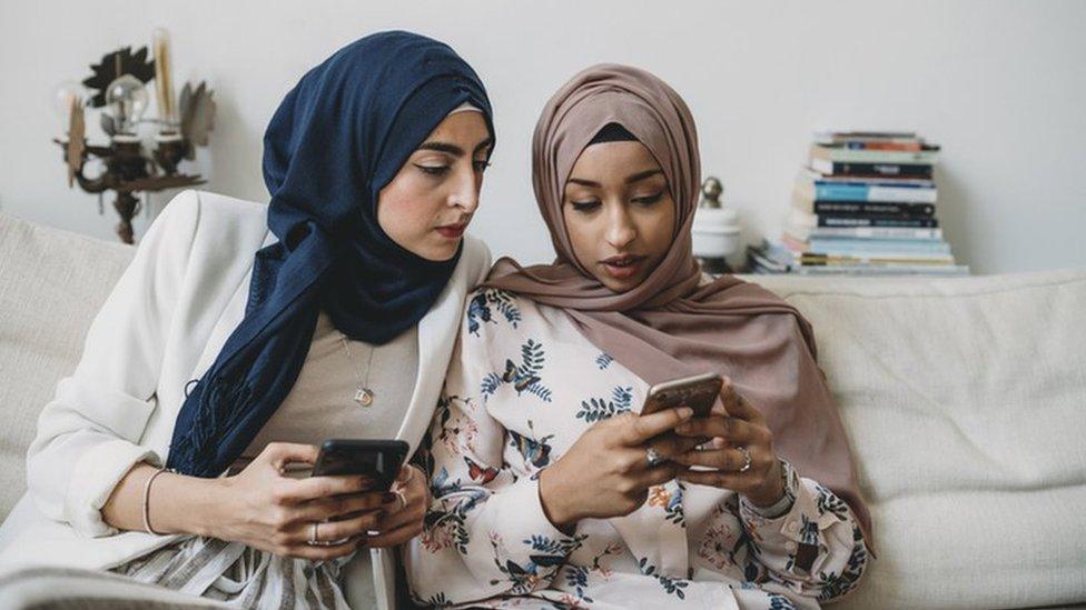 امرأتان عربيتان تنظران في هاتفيهما المحمولين