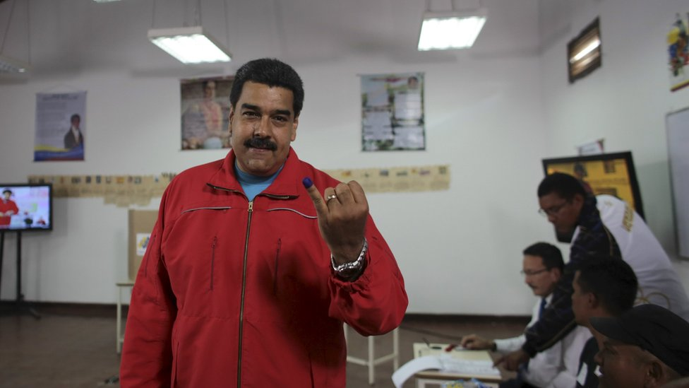 Nicolas Maduro shows his ink-stained finger after casting his vote