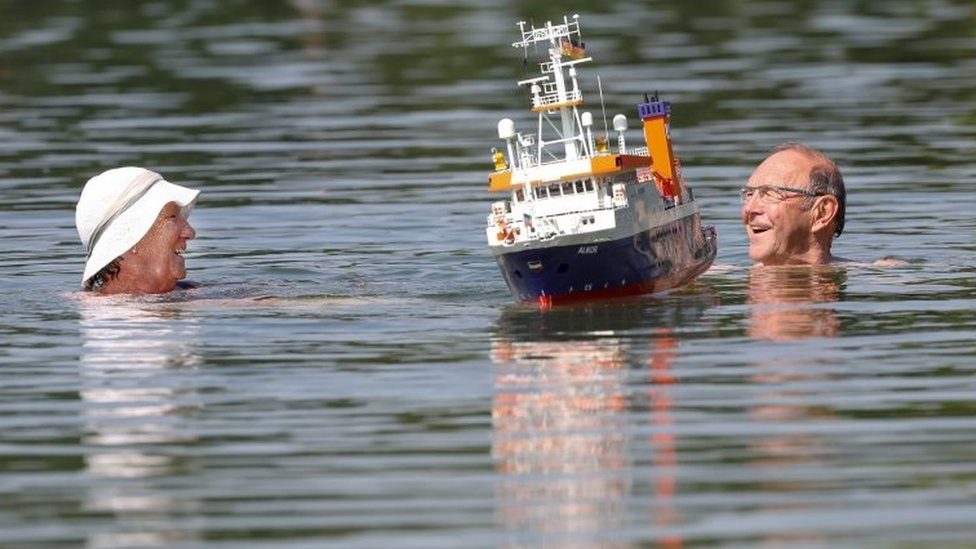 A couple swim past a model boat at the Schwarzachtal lakes in southern Germany