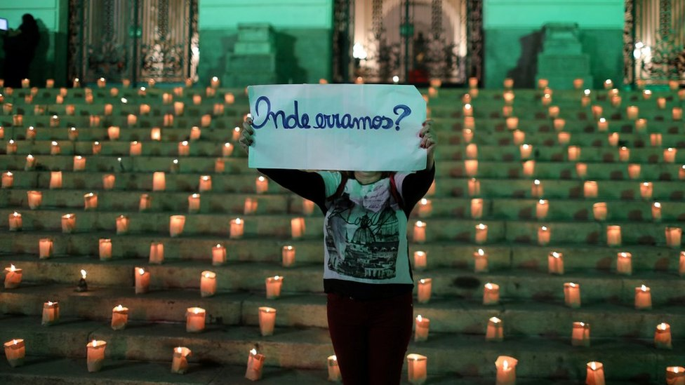 """A protester against the government's policies holds a placard saying, """"Where did we go wrong?"""""""