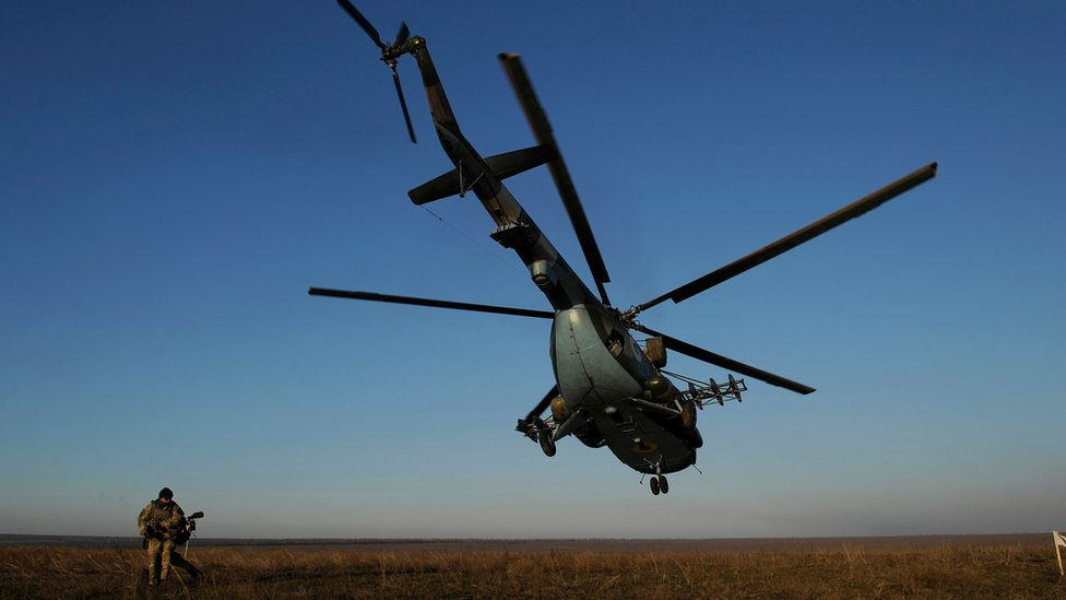 A serviceman walks near a Ukrainian military helicopter flying during military drills on an open green space with blue skies