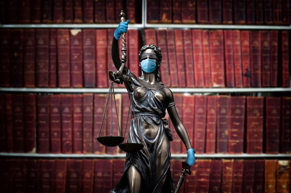 Estatua de la justicia con mascarilla y guantes de latex