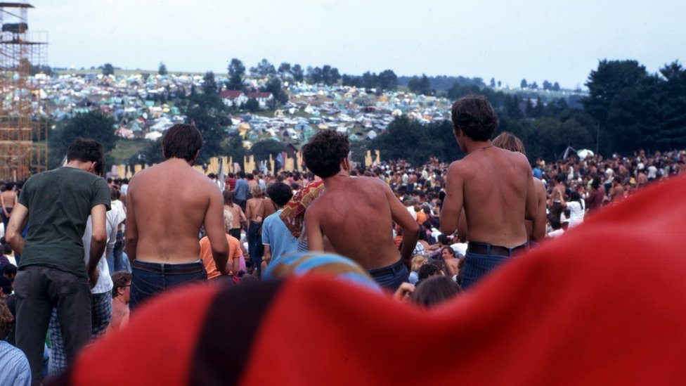 Three sunburned men stood up in front of a large crowd of people