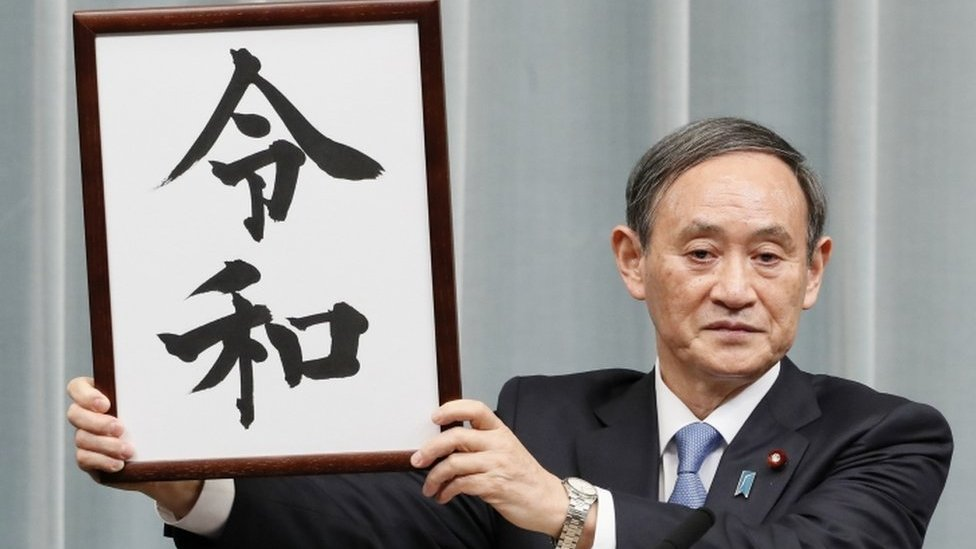 "Japan's Chief Cabinet Secretary Yoshihide Suga unveils the new era name ""Reiwa"" at a news conference in Tokyo on 1 April, 2019"