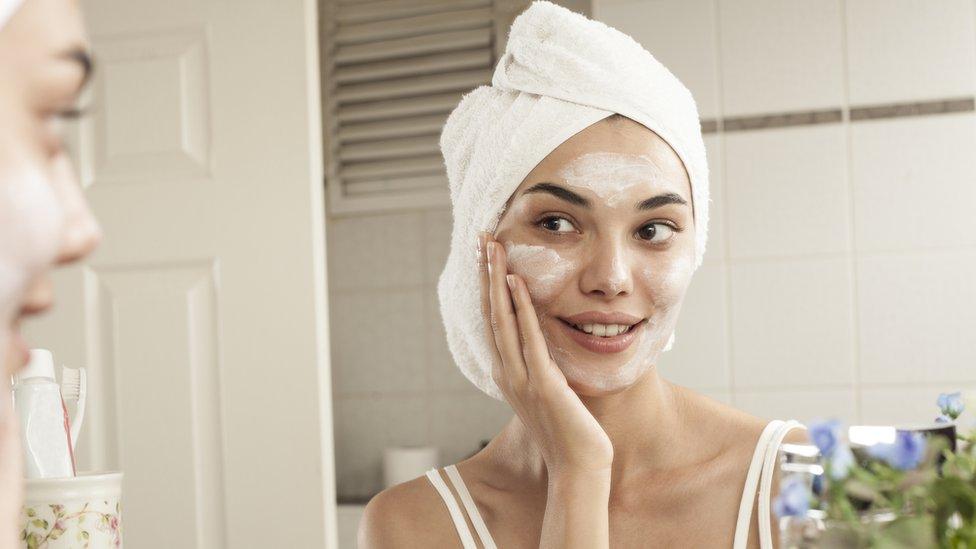 Una mujer poniéndose una crema en el rostro.
