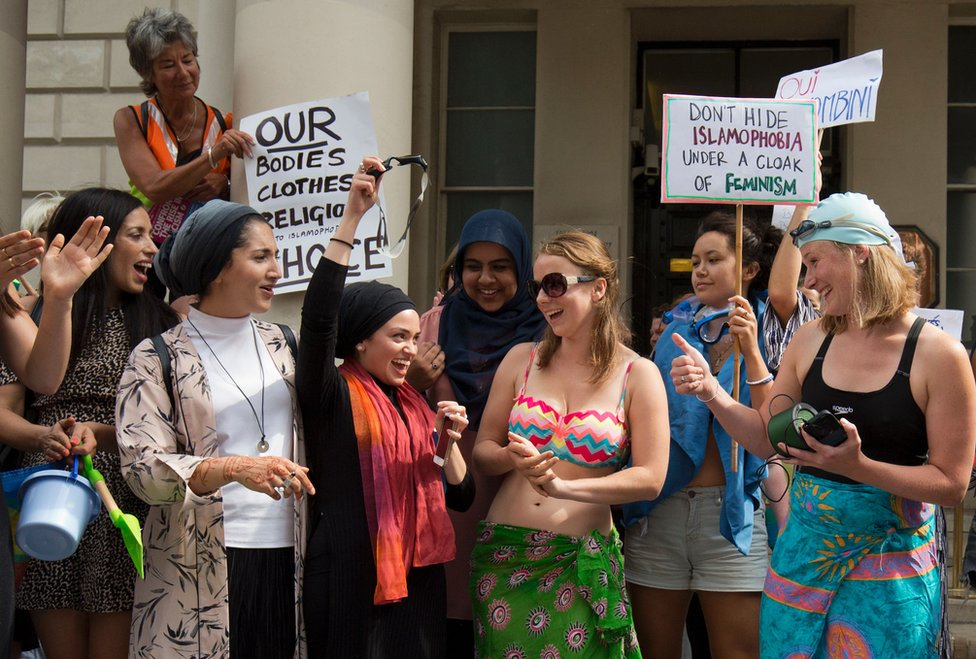 women in loads of different types of clothes (one in a bikini, some in head coverings) laugh and clap together