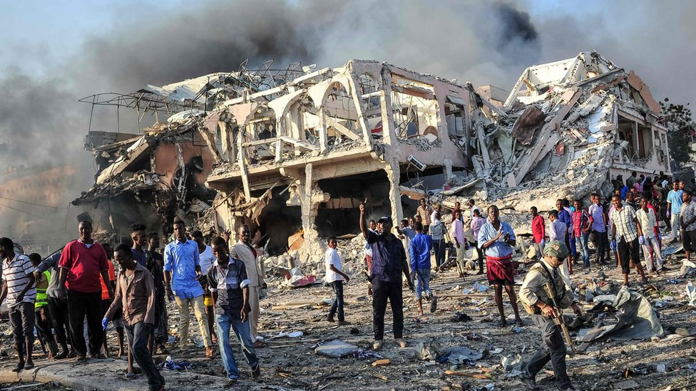 Men and Somali soldiers arrive on the site to rescue victims of the explosion of a truck bomb in the centre of Mogadishu, on 14 October 2017