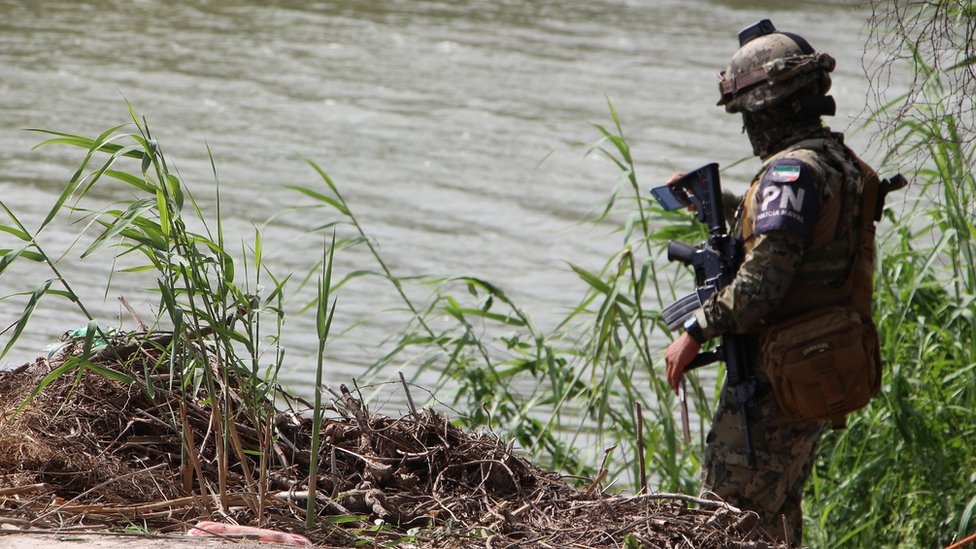 A member of the Mexican Police patrol the area where the dead bodies of a presumed migrant and his baby were found