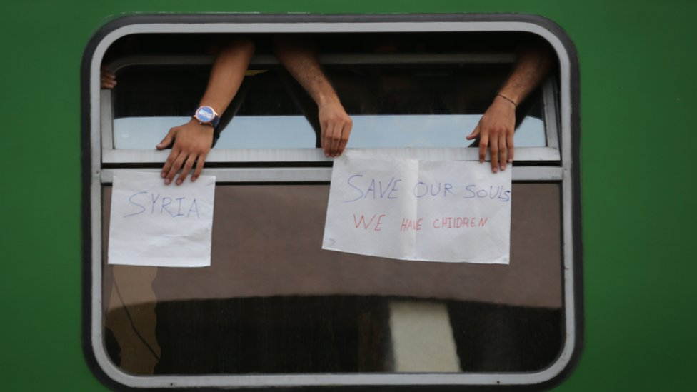 """People on train at Budapest Railway Station hold signs saying """"Save our souls"""""""