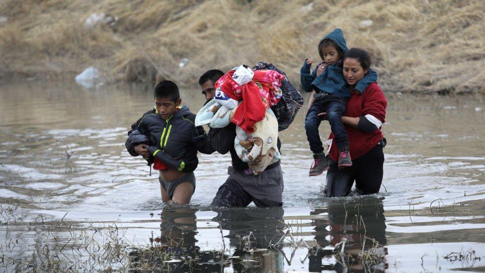 Inmigrantes cruzando un río
