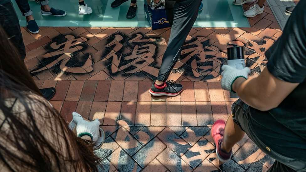 Students protesters walk over a graffiti slogan on the ground as they take part in the Occupy University Street rally