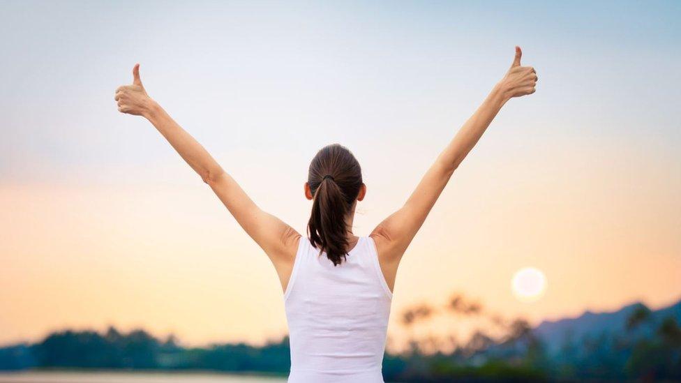Mujer alzando los brazos