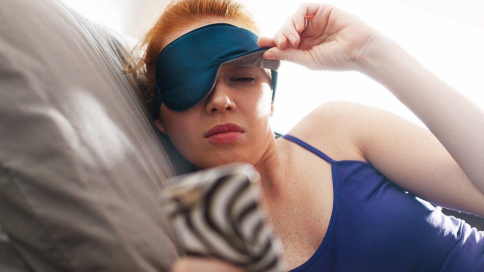 Mujer con antifaz despertándose.