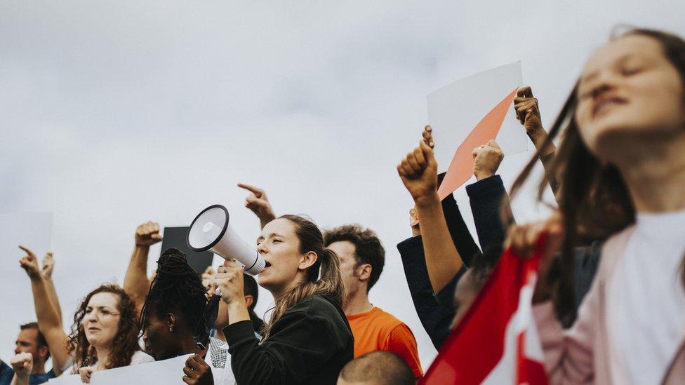 Jovens ao ar livre protestando com megafones e cartazes