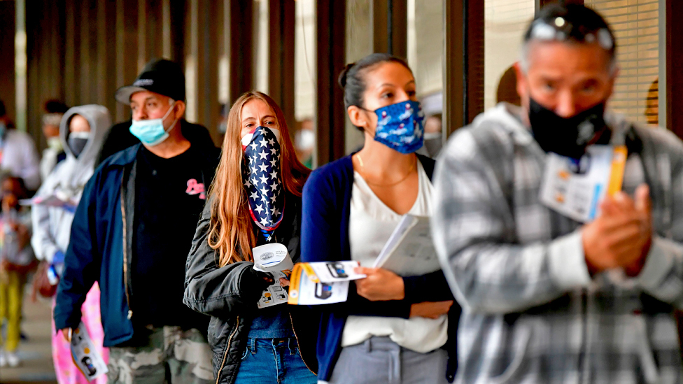 Voters wear face coverings while queuing to vote in the 2020 US elections at the Los Angeles County Registrar in Norwalk, California