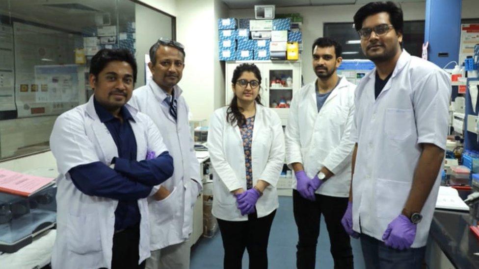 Cinco cientistas de jaleco e laboratório