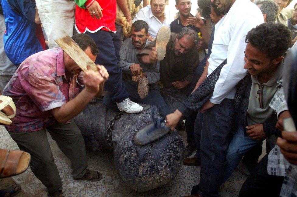 بعد اسقاط تمثال صدام في بغداد انتشرت صور لأشخاص يضربون رأس التمثال بأحذيتهم