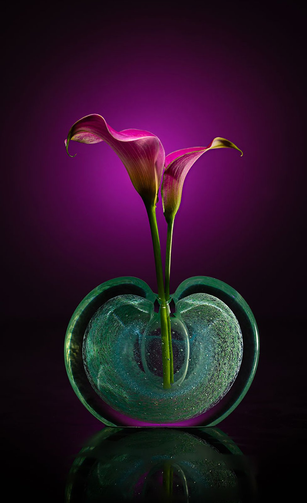 Two flowers in a perfume bottle with a dark purple background