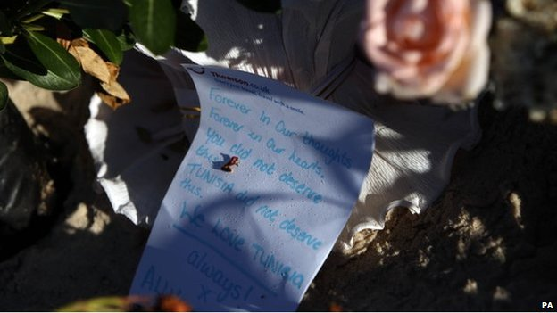 Flowers and letter in memory of victims on Sousse beach