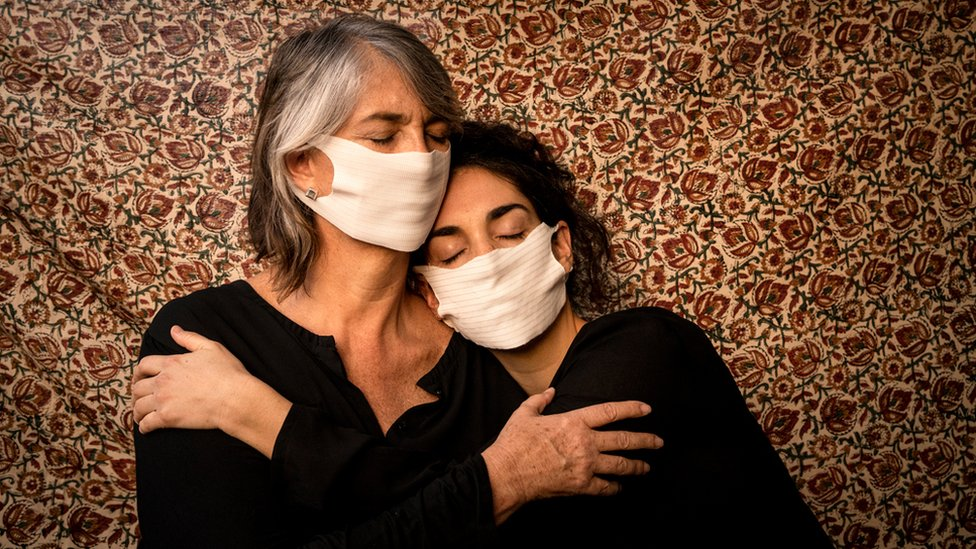 Two women embrace, wearing face masks