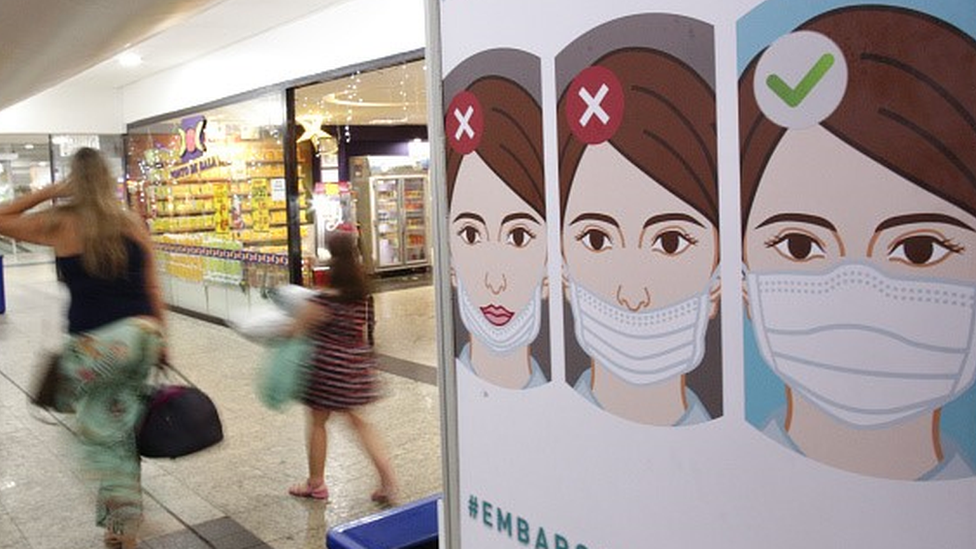 Panel informativo sobre el uso correcto de mascarillas en un aeropuerto.