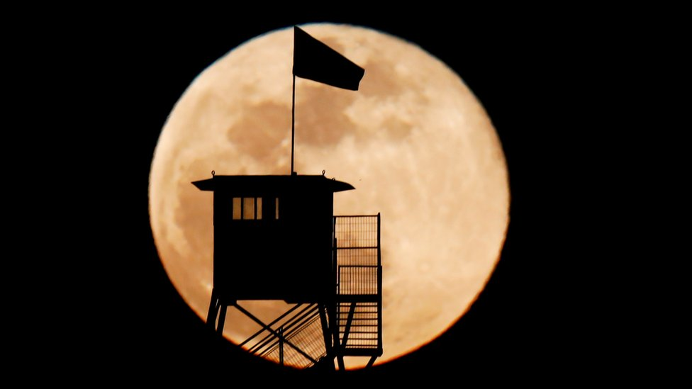 A ranger's tower is silhouetted over a Supermoon near Ruhama in south Israel