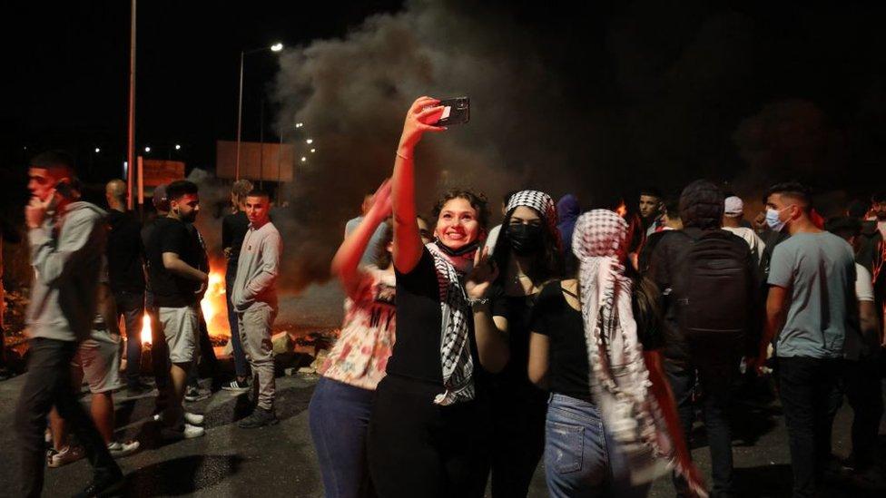 متظاهرون فلسطينيون يلتقطون صورة سيلفي