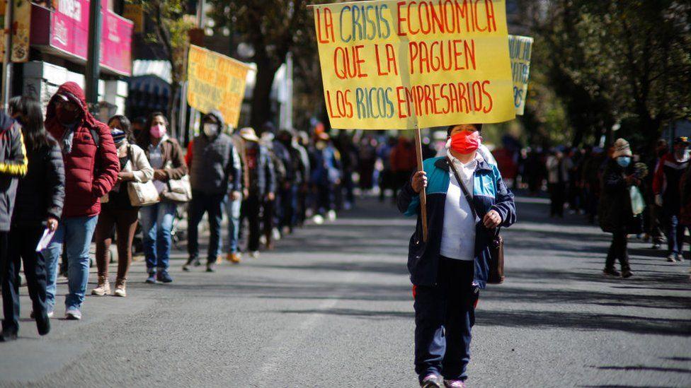 Una mujer con una mascarilla en una manifestación