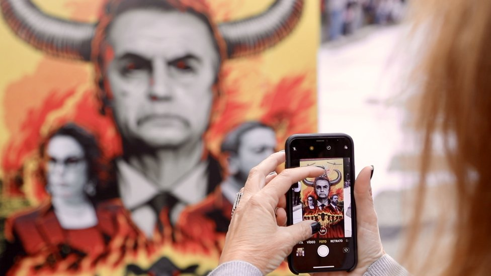 Protester takes picture of image depicting President Bolsonaro