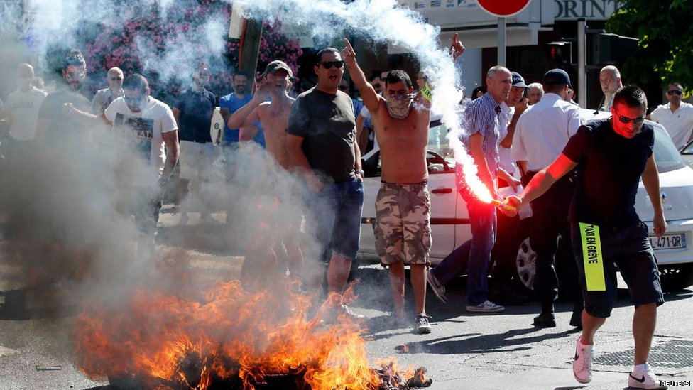 Taxi drivers on strike burn tyres during a national protest against car-sharing service Uber in Marseille, France, June 25, 2015.