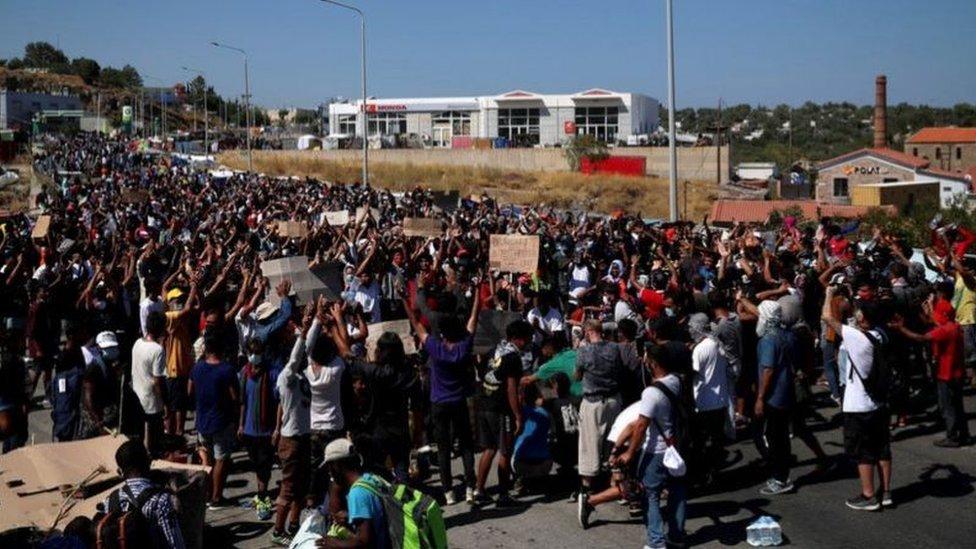 مهاجرون يحتجون على بناء مخيم جديد في موقع المخيم المحترق