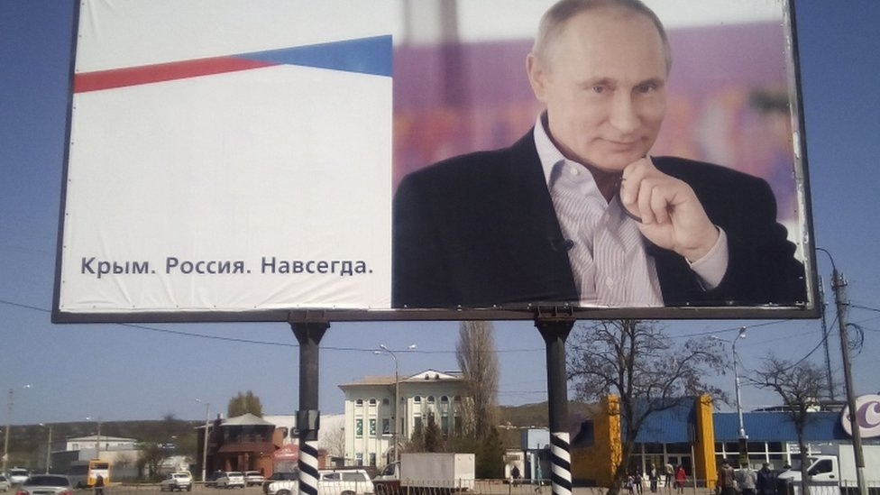 """A billboard with a portrait of Russian President Vladimir Putin is displayed on a street in Kerch, Crimea, April 016. The board reads: """"Crimea. Russia. Forever."""""""