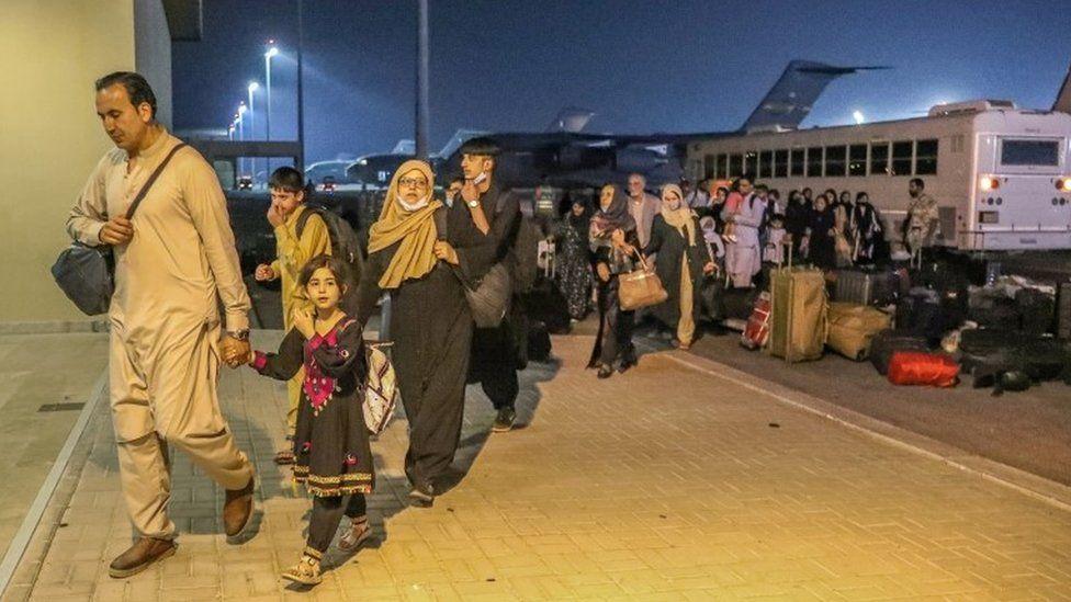 أشخاص تم إجلاؤهم من أفغانستان لدى وصولهم إلى قاعدة العيديد الأميركية في قطر.