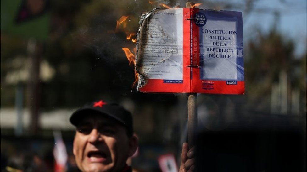 A demonstrator burns a Chilean constitution during a march and protest on the anniversary of the 1973 Chilean military coup, in Santiago, Chile September 11, 2020