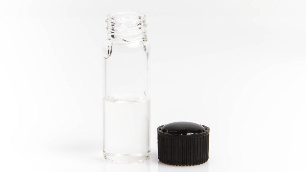 Botella conteniendo un líquido incoloro.