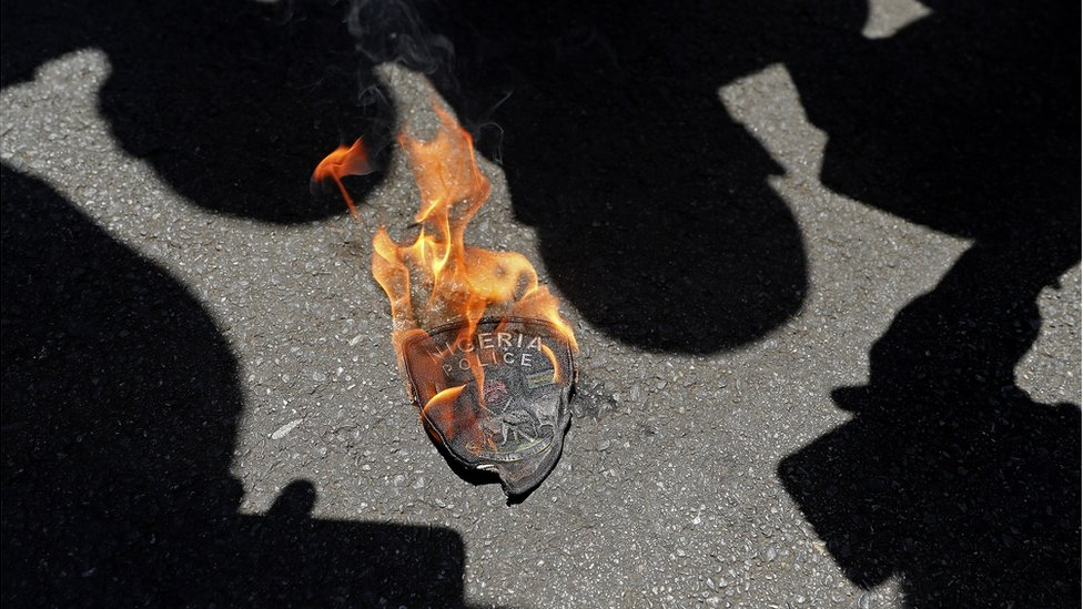 A Nigerian police emblem is seen burning during a protest outside their embassy in Pretoria